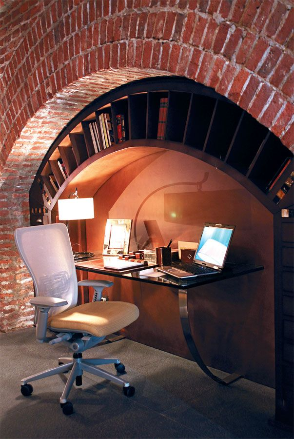 Este espacio de trabajo ideado por la diseñadora Diana Gradel saca provecho de uno de los arcos de una antigua construcción para dar vida a un rincón ultra original. Bajo la pared revestida en ladrillo, la biblioteca reproduce la forma del arco y tiene estantes y nichos para libros y papeles. Completan esta propuesta escenográfica un escritorio de líneas modernas en vidrio y acero, y un sillón tecnológico de Hasworth (Manifesto).