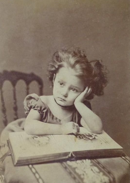 Little girl with a book,1870. The same way kids look today when you ask them to read. Sad thing is this little girl probably could read. Many teenagers today come out of school barely able to do so.