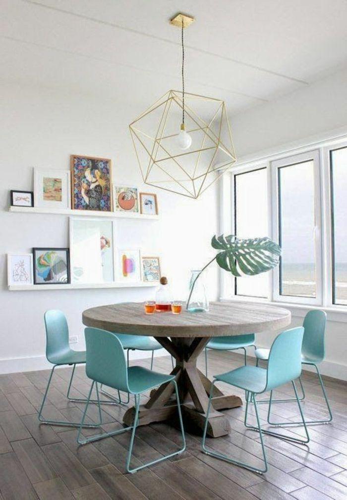 decoracion salon, comedor con mesa de madera, sillas azules, lámpara colgante. estanterías con cuadros, parqué