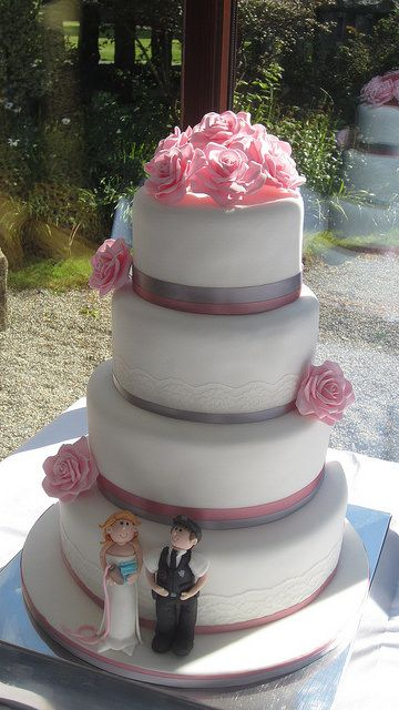Pink rose themed wedding cake with bride & groom figures