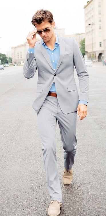 Comprar ropa de este look:  https://lookastic.es/moda-hombre/looks/traje-camisa-de-manga-larga-botas-safari-correa-gafas-de-sol/3147  — Camisa de Manga Larga Celeste  — Traje Gris  — Correa de Cuero Marrón  — Gafas de Sol Marrón Oscuro  — Botas Safari de Ante Beige