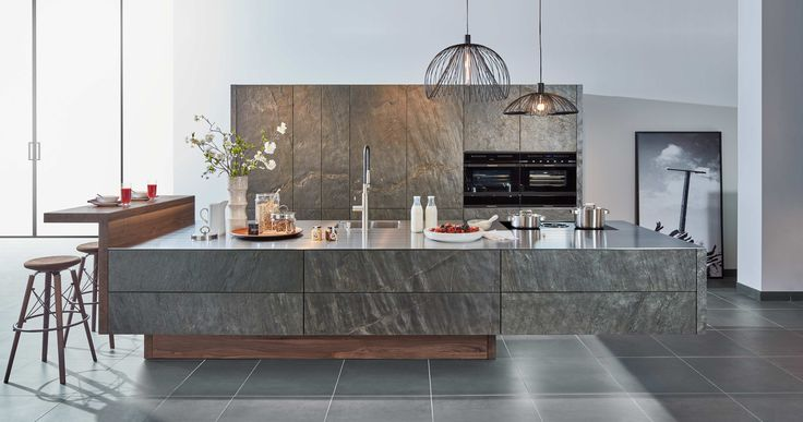 A real stone kitchen with zeyko-Flybridge appears to be design outweighing physics.  The weight of the suspended kitchen block in real ocean green stone veneer seems to be lifted by the overhang alone. The correspondence of the shimmering, real stone with the barely 4mm thick stainless steel panel and the applications in walnut wood result in a harmonious dialogue created by real materials. This is rounded off by the perfectly harmonising interior fittings, zeyko inline in solid walnut…