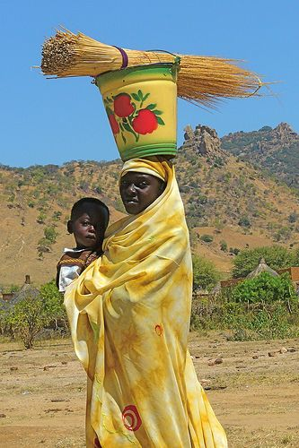 Africa | Portrait of an woman carrying a child and a bucket on her head, Sudan | Rita Willaert