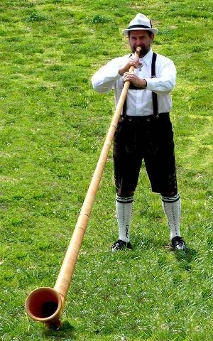 Musician playing the Alphorn. SWITZERLAND. The alphorn, alpenhorn or alpine horn is mostly associated with Switzerland and the Alps, but similar wooden horns have been used in most of Europe's mountainous regions over the centuries