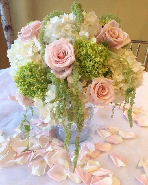 Simply elegant wedding arrangement.  Short cylinder vase with green hydrangeas soft pink roses , white hydrangeas with green hanging amaranthus .