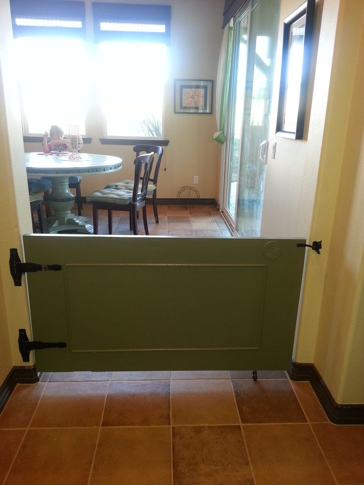 Custom made gate for our kitchen (doggie gate for giant puppy). We made it out of a used hollow door and added decorative wood trim. Since the door is long, we added a caster wheel on the bottom for support.
