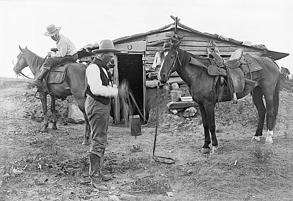 "George Pattullo (mounted) waits for Harry Campbell before the doorway of his father, Judge Henry ""Paint"" Campbell. ""Paint"" was the founder of the Matadors and ""holed up"" here in this Matador line camp after retirement. Matador Ranch, Texas., 1908 Gelatin dry plate negative EES www.cartermuseum.org"