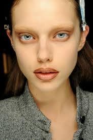 Gebleekte wenkbrauwen  Door de wenkbrauwen te bleken, gaat de aandacht naar andere gezichtskenmerken zoals de ogen, de lippen en de vorm van het gezicht. Bij Gucci waren de gezichten en de wenkbrauwen van de modellen spierwit gemaakt. Miu Miu benaderde de ogen en de huid erom heen als een schilderij en versierde deze met witte en turquoise sierkrullen en spiegelende, grote pailletten. Versace wilde alleen focus op de zwart omrande ogen