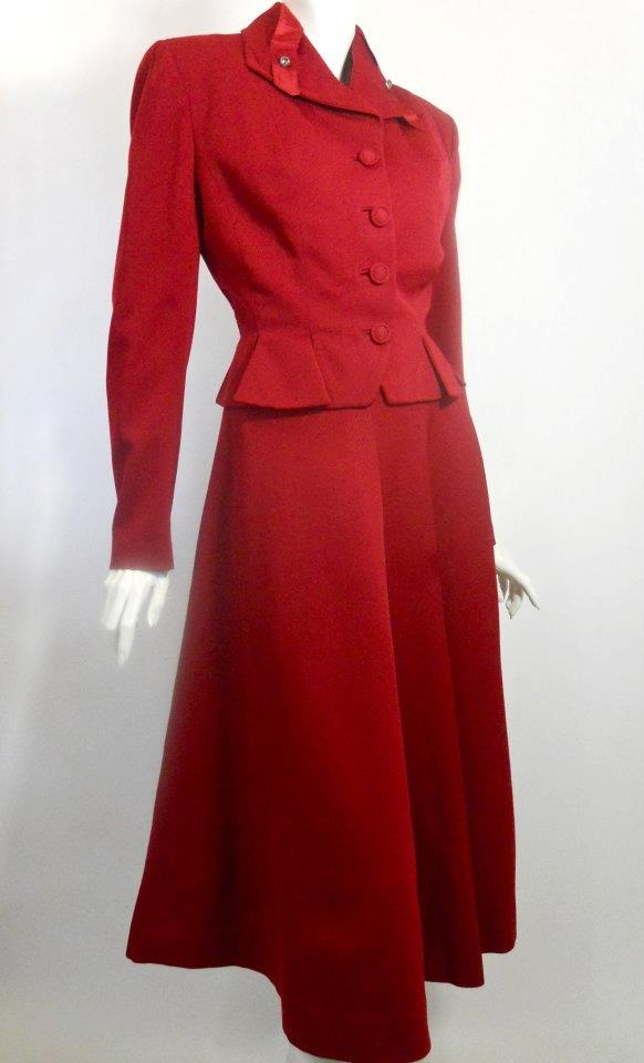 Deep cherry red gabardine late 40s suit by Lilli Ann. Notched short peplum below nipped waist, covered buttons, ribbon and rhinestones on collar. Skirt is semi full creating a silhouette reminscent of the New Look.
