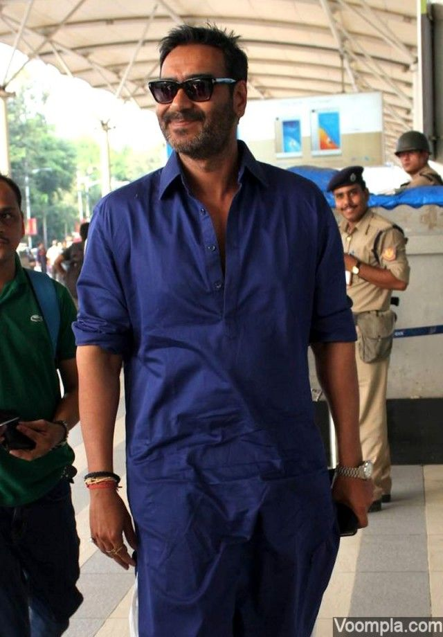 Ajay Devgn spotted at Mumbai airport looking stylish in a blue pathani and black Wayfarer style sunglasses. via Voompla.com
