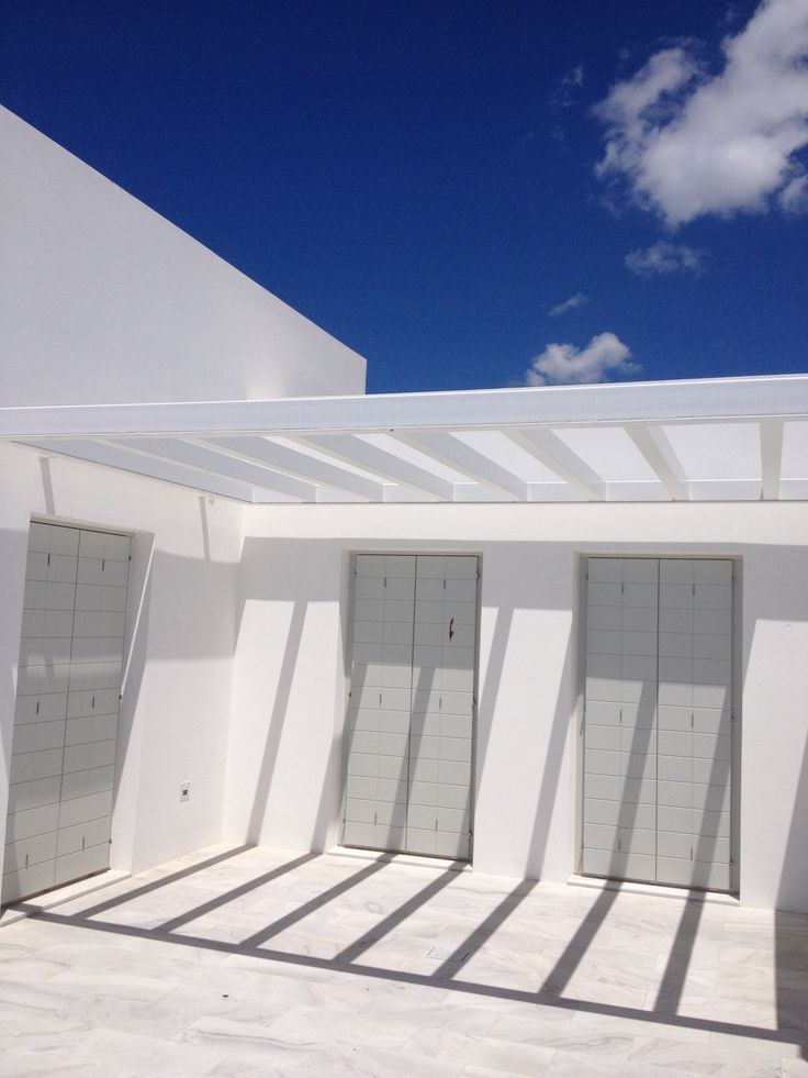 colors of white, blue and light gray in the island of Paros, Greece. Wooden shutters and pergola made with Accoya wood