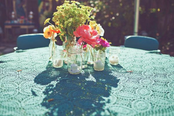3 or 4 jars per table, one with a mixed bouquet, the others with just one kind of flower in each different jar