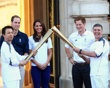 Prince William, Duke of Cambridge, Catherine, Duchess of Cambridge and Prince Harry watch Wai-Ming hand over the London 2012 Olympic Torch to John Hulse during a visit to Buckingham Palace during Day 69 of the London 2012 Olympic Torch Relay on July 26, 2012 in London, England. The Olympic flame is making its way through the capital on the penultimate day of its journey around the UK before arriving in the Olympic Stadium on Friday evening