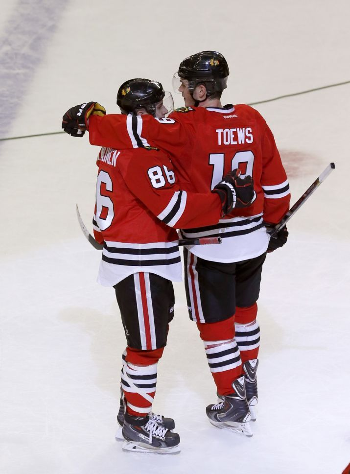 Chicago Blackhawks team captain, Jonathan Toews (19), puts his arm around rookie Teuvo Teravainen, after Teravainen's first NHL hockey game, against the Dallas Stars Tuesday, March 25, 2014, in Chicago. The Blackhawks won 4-2.