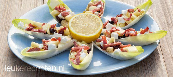 Witlofschuitjes met appel en spek VOORGERECHT/HAPJE – 15 MINUTEN – 8 STUKS *  Heerlijke appetizer; witlof met zoete appel, hazelnoten en geitenkaas in combinatie met zoute spekjes  Ingrediënten 8 mooie blaadjes witlof 2 eetl hazelnoten 3 eetl rozijnen 1 appel 50 gr gebakken spekreepjes  ½ citroen 1 eetl olijfolie 50 gr zachte geitenkaas Zwarte peper ½ eetl honing