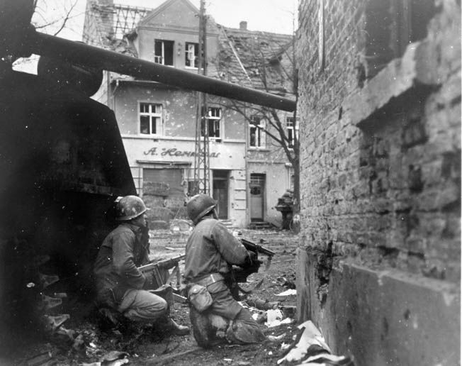 On December 17, 1944, as the German juggernaut rolls forward during the Battle of the Bulge, two infantrymen of the American 83rd Division, both armed with Thompson submachine guns, peer around a corner in the rubble-strewn streets of Gurzenich, Germany.