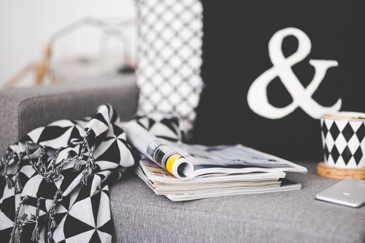 Close of magazines, mug and phone on a couch · Free Stock Photo