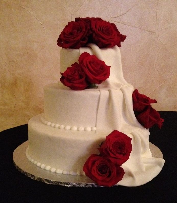 Rose Wedding Cake - Buttercream icing with fondant draping and fresh roses. I was shown a picture of this cake by a bride who asked me to recreate it.  I do not know the name of the original designer but I want to give credit where credit is due.  Thank you for the design.