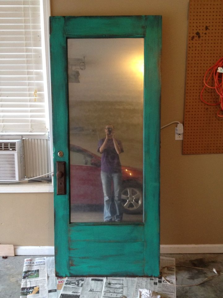 "This old door found @Anything Goes Trading Co was turned into a full length mirror. It had a glass pane, so I cleaned it and used spray paint to transform the glass into an ""antique looking"" mirror. You can use spray paint to turn glass panes in windows (or doors) into mirrors."