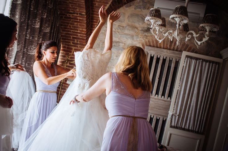 The bridesmaids help the bride with the wedding dress.