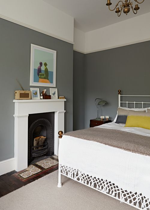 Reclaimed fireplace with original hearth tiles. Walls painted in Farrow & Ball 'Plummet'. Iron bedstead with vintage blanket.