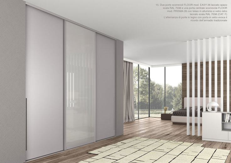 Due porte scorrevoli FLOOR mod. EASY 26 laccato opaco scala RAL 7038 e una porta centrale scorrevole FLOOR mod. PRISMA26 con telaio in alluminio e vetro retro laccato scala RAL 7038. L'alternanza di porte in legno con in vetro evoca il ricordo dell'armadio tradizionale. By ZEMMA