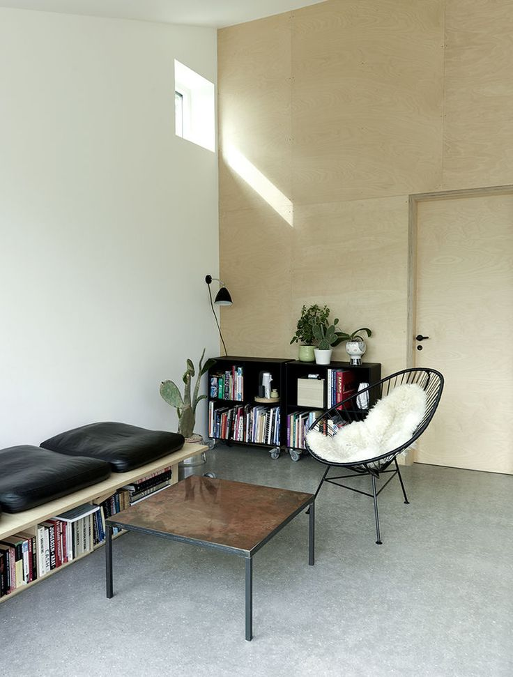 Hoop chair + sheepskin; square black leather cushions on storage bench; birch plywood wall