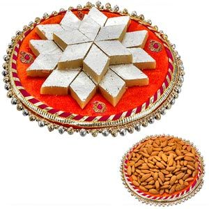 Shagun Thaali :  Delightful velvet thaali covered with paisley motifs, golden lace and lined with golden beads. This pack contains: Kaju katli. Net weight: 200 grams. American almonds. Net weight: 50 grams. Comes with rakhi, roli and chawal. Net weight of goodies: 250 grams. Almonds are packed in decorative pouch. Rs 676/- Shop Now : http://www.tajonline.com/rakhi-gifts/product/r4526/shagun-thaali/?aff=pint2014/