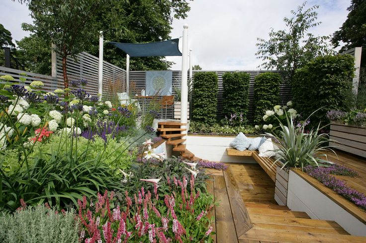 This garden space has several small, connected seating areas. Built-in benches flow into a short staircase to a raised dining platform. Planting beds tucked between and behind the seating areas help the compact garden feel surprisingly roomy. Contemporary Deck by Helen Williams Garden Design
