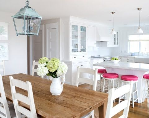 I love the beach lantern above the table & how those hot pink stools pop against the white walls!