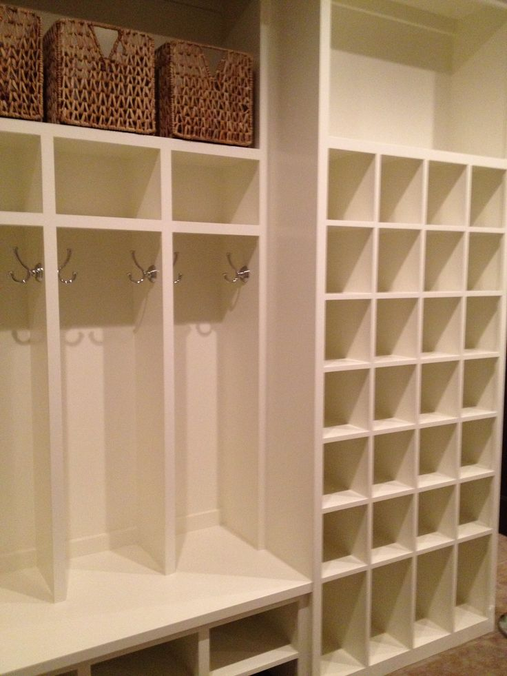 this mud room has open cabinets a lot of shoe storage area white colour