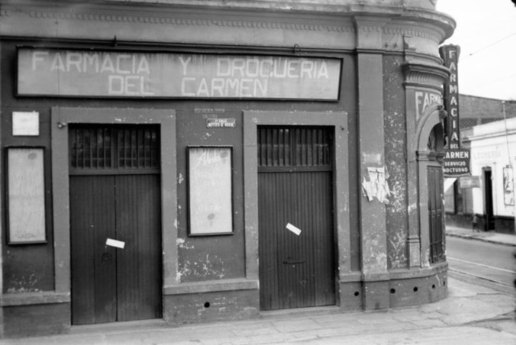 """La farmacia y droguería """"Del Carmen"""", ubicada en la esquina de la Calzada México-Tacuba y la calle del Instituto de Higiene, frente al Árbol de la Noche Triste, en Popotla. Esta construcción aún existe y sigue siendo farmacia, ahora llamada """"Del Árbol""""; a la derecha podemos ver el ancho original que tenía la calzada, los rieles del tranvía a Azcapotzalco y una lechería en la acera de enfrente."""