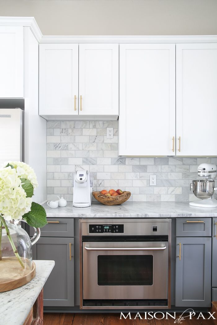 Two-toned gray and white cabinets, marble subway tile, Carrara countertops, a big farmhouse sink, and brass hardware give this kitchen a classic yet modern look.