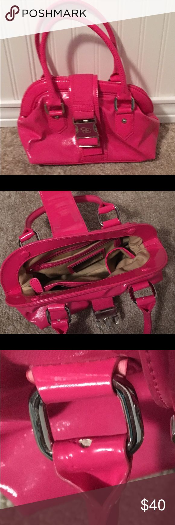 """Jessica Simpson Hot Pink Handbag Jessica Simpson. Hot Barbie Pink. Silver Hardware. Plastic-Like Material. Interior Snap Closure with Pink Exterior Flap featuring a Silver Buckle Closure. Slight Wear on the Inside Handles (as pictured, due to the fabric rubbing against each other). Handle Defects are not Visible From the Exterior. Jessica Simpson Logo across the Bottom of the Bag. Bag Features Tiny Silver Feet at the Button to avoid Damage. Measurements : 7"""" Height, 11"""" Length. Perfect for…"""
