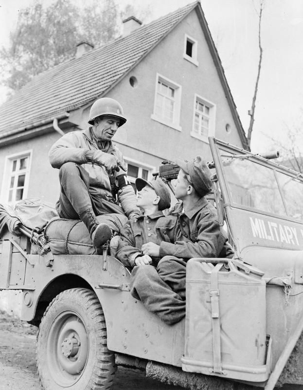 A US military policeman talks to two German boy POWs, who have been loaded unto the Jeep for the quick ride to the detention area. Children as young as 12 were often caught in the net of the army in the last few months of the war as manpower shortages had become dramatic. The history of these unfortunate children has yet to be comprehensively told.