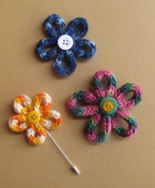 Instrucciones y fotografias para hacer flores con lana, que podemos usar como broches o adornos.