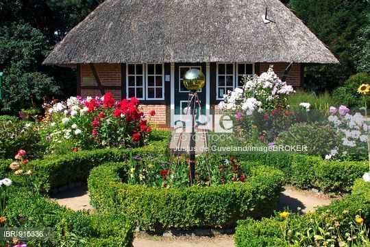 Stock Photo: Low German cottage garden with thatched garden house, boxwood hedges, boxwood circular flowerbed, Phlox (Phlox paniculata) and other summer flowers.