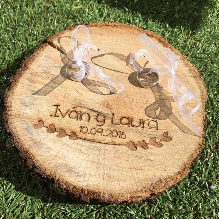 Un original porta-alianzas sobre una rodaja de árbol natural. Con grabado de una guirnalda bajo vuestros nombres y la fecha del evento.