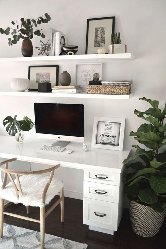 Hjemmekontor med hvidt skrivebord og grønne planter.