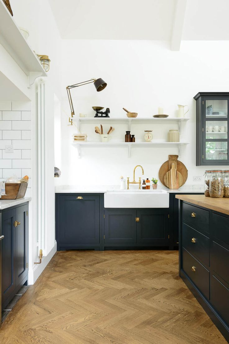 navy cabinets + chevron floor + wall shelves + swing arm light