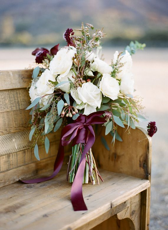The bridesmaids will carry loose bouquets of ivory spray rose, purple parvifolia, white stock flowers, dark pink astrantia, burgundy scabiosa, greenery, silver dollar eucalyptus, burgundy ammi, and jasmine vine wrapped in champagne ribbon with the stem showing