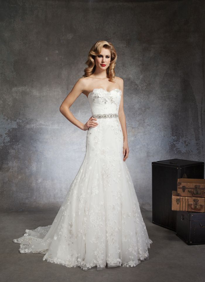 Justin Alexander wedding dresses style 8663    A draped lace sweetheart neckline with 3D flowers of tulle, ribbons and  beading accent this tulle and lace mermaid. An attached belt of beading  and metallic threads creates a flower pattern. Buttons cover the back  zipper to the drop waist and this style has a chapel length train.