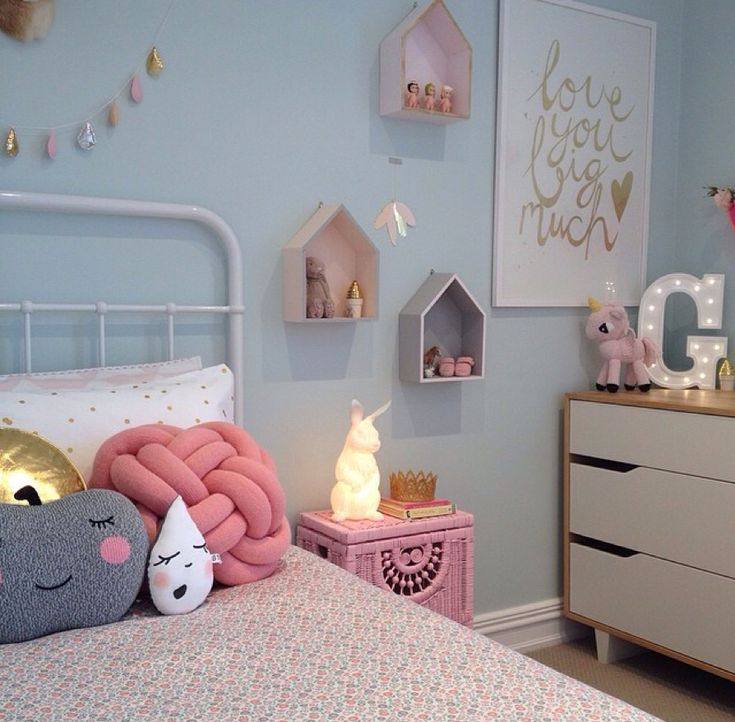 Seriously cute kids room with light blue walls and pale pink and white accents.