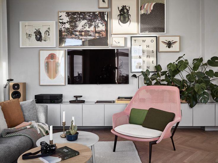 Jonas Wagells lägenhet. Inredningsinspiration på Södermalm. Tavelvägg och ljusgrå möbler, rosa fåtölj och monstera.