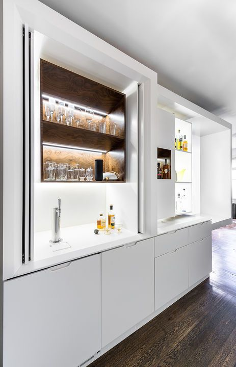"Exterior doors slide open and tuck to the side to reveal shelving for liqour bottles and glassware and a beer tap. ""When you're designing a kitchen you can get away with a lot more because there is an expectation that it's a functional space,"" Chen says. ""But in a thing like a bar—particularly one that isn't active all the time—I think there's a pretty big challenge to incorporating the service aspects without it reading like a kitchen."""