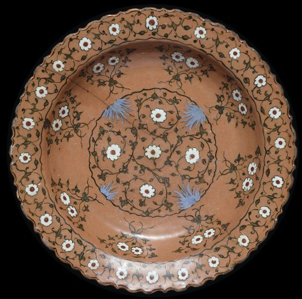 Dish | Iznik, Turkey, ca. 1550-1560 | Fritware, covered in salmon-pink slip, polychrome underglaze painted, and glazed | This large dish is a good example of Iznik ware with a coloured ground. In the 1550s, potters in Iznik in Turkey were using a variety of coloured slips (liquid clay) to cover the bodies of their wares. They then added detailed designs in slips of contrasting colours and paint | VA Museum, London