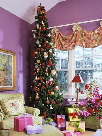 Stylishly Skinny Tree:   Fun and whimsical, this slender tree is perfect for rooms with tall ceilings. Fill the branches with oversize retro-inspired ornaments and smaller bold-color ornaments. Complete the look with bursts of colorfully wrapped packages.