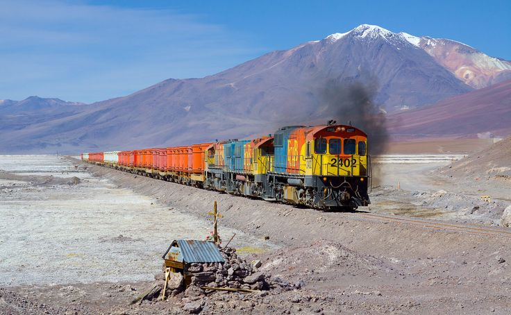 "Three Ferrocarril Arica-Bolivia (FCAB) engines with a ""bucket train"" crossing the Salar de Ascotan (salt lake Ascotan) on their journey from Calama to Ollagüe (at the Bolivian border), Chile. The buckets are probably empty; they are used to transport ore from Bolivia to the ports of Chile. The engines are EMD GR12 2402, EMD/Clyde GL26C-2 2010 and EMD/Clyde GL26C-2 2005. In the background you can see the 5846 m high stratovolcano ""Cerro del Azufre""."