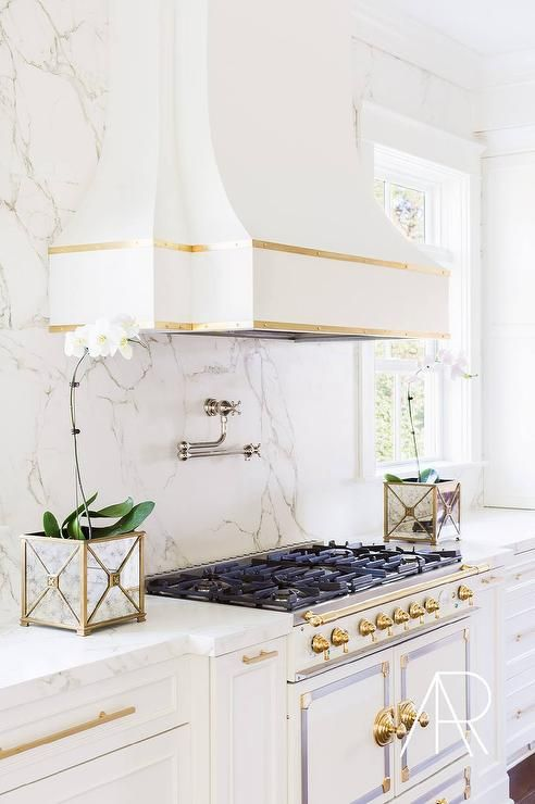 White and gold kitchen features white cabinets adorned with long gold pulls paired with Silestone countertops and backsplash that resemble white marble.
