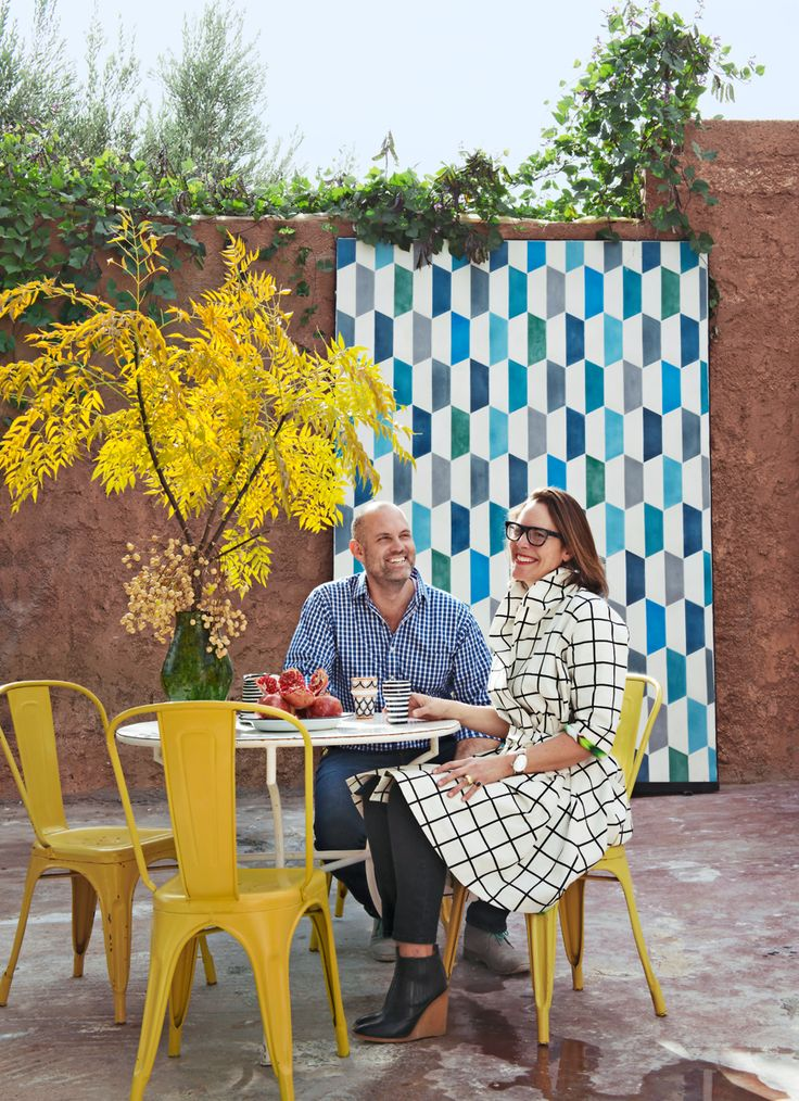 Caitlin e Samuel di  Popham Design nel cortile della loro casa-atelier di Marrakech. Sedie da esterno Chaise A di Tolix. Sul fondo un grande pattern grafico in ceramica /// Caitlin and Samuel of  Popham Design in the courtyard of their atelier-house in Marrakech. Chaise A Chairs by Tolix. In the background a big ceramic graphic pattern • Photo Nicolas Matheus